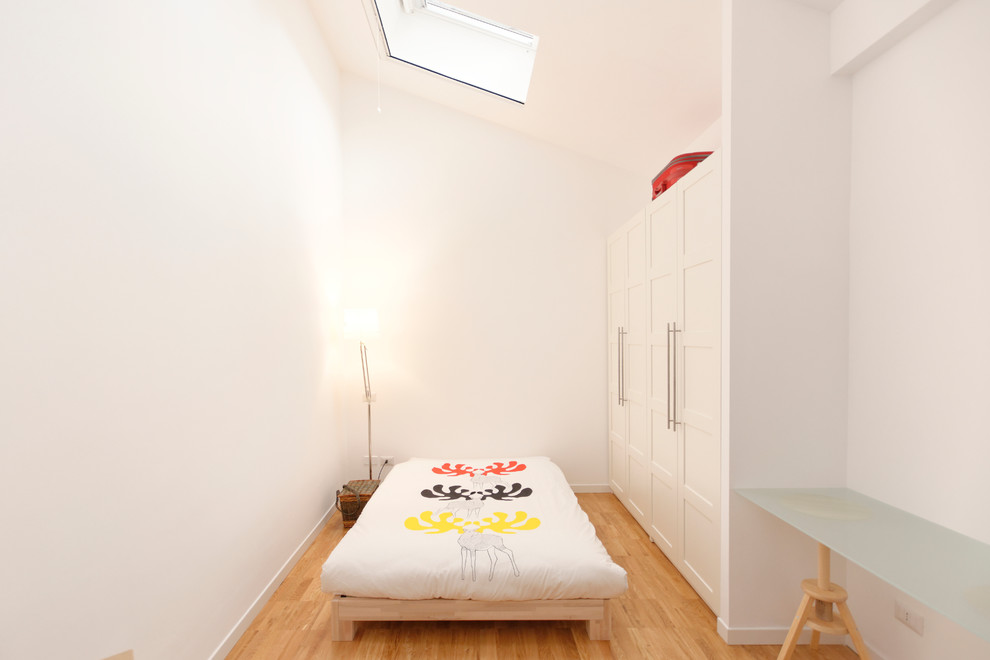 Mid-sized danish light wood floor bedroom photo in Milan with white walls