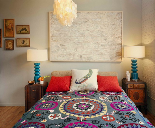 This is an example of a bohemian bedroom in New York with beige walls and medium hardwood flooring.