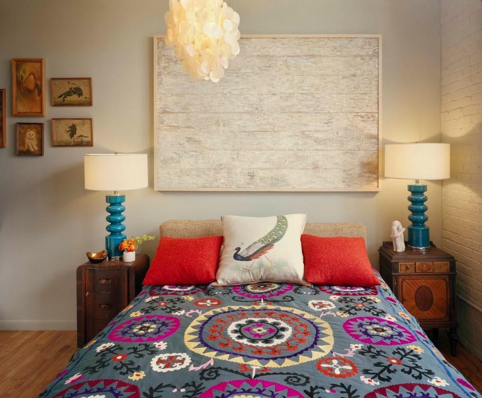 Example of an eclectic medium tone wood floor bedroom design in New York with beige walls