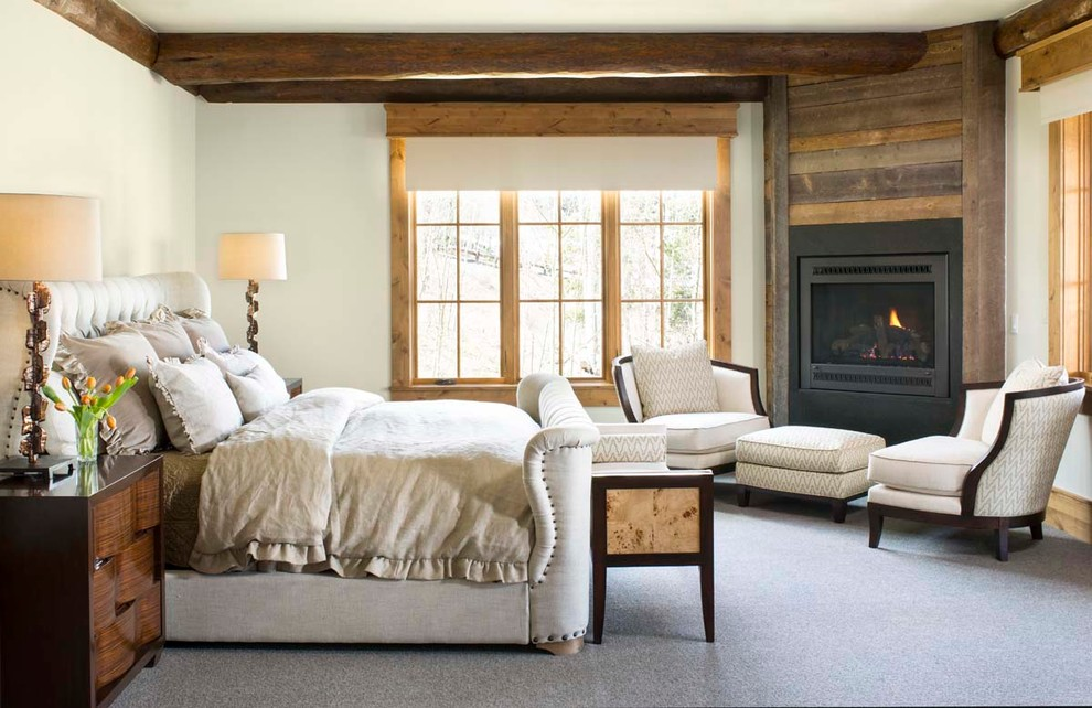 Example of a large mountain style master carpeted bedroom design in Denver with white walls and a corner fireplace