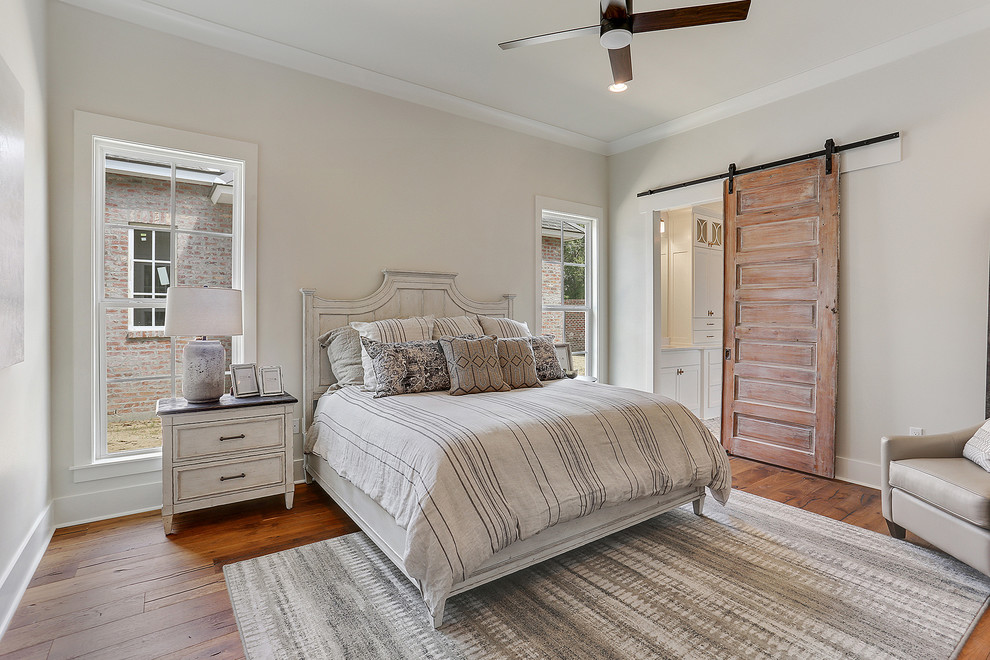 Inspiration for a mid-sized timeless guest dark wood floor and brown floor bedroom remodel in New Orleans with beige walls and no fireplace