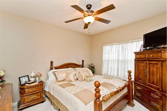 Example of a large classic carpeted bedroom design in Columbus with beige walls and no fireplace