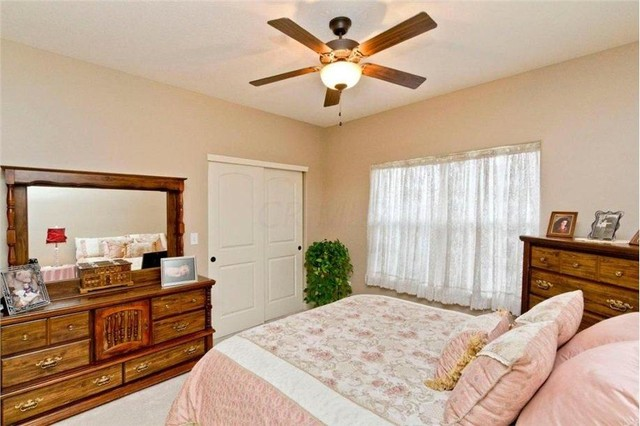 Large elegant carpeted bedroom photo in Columbus with beige walls and no fireplace