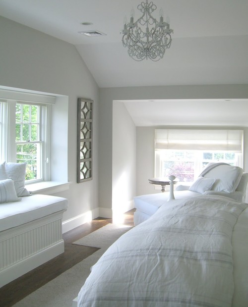 bedroom with dormer window and small white chandelier painted in light pewter