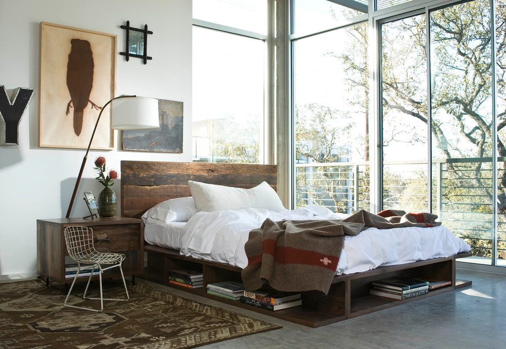 This is an example of an urban bedroom in Los Angeles with white walls, concrete flooring and grey floors.