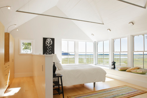 A mostly white bedroom with wrap around windows.