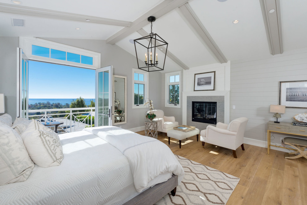 Large beach style master medium tone wood floor and brown floor bedroom photo in Los Angeles with gray walls, a standard fireplace and a tile fireplace