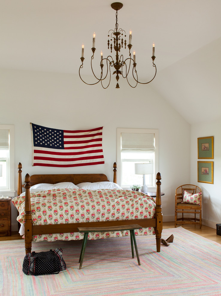 Example of a beach style medium tone wood floor bedroom design in New York with white walls