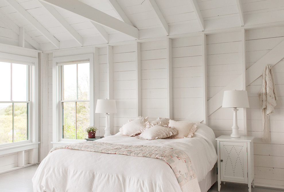 Example of a beach style painted wood floor and white floor bedroom design in New York with white walls