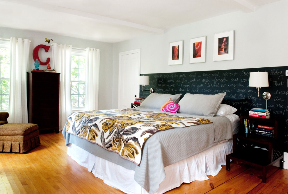 Example of an eclectic medium tone wood floor bedroom design in Boston with white walls
