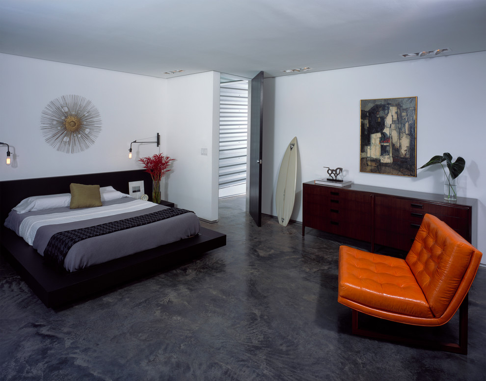 Example of a minimalist concrete floor and black floor bedroom design in New Orleans with white walls