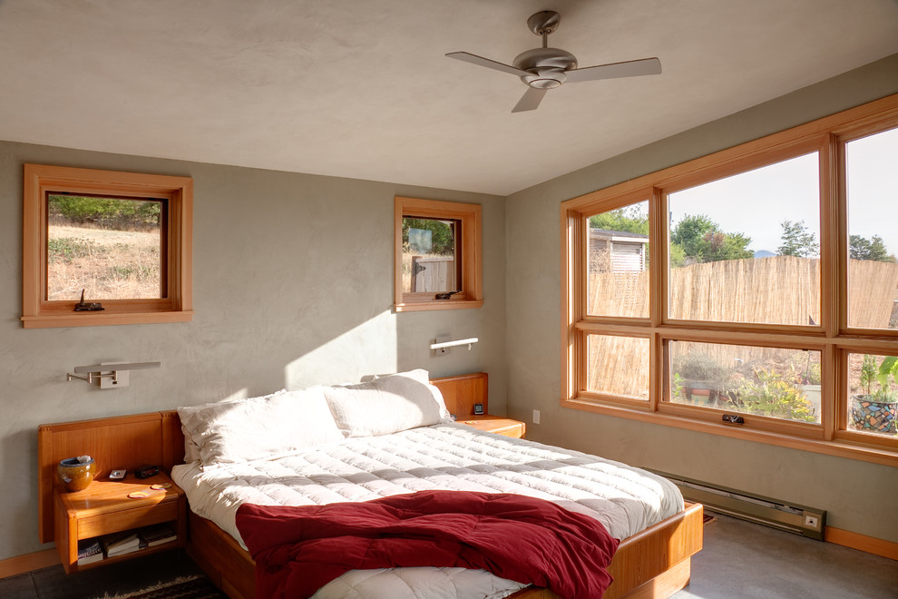 Example of a mid-sized trendy master concrete floor and gray floor bedroom design in Other with gray walls