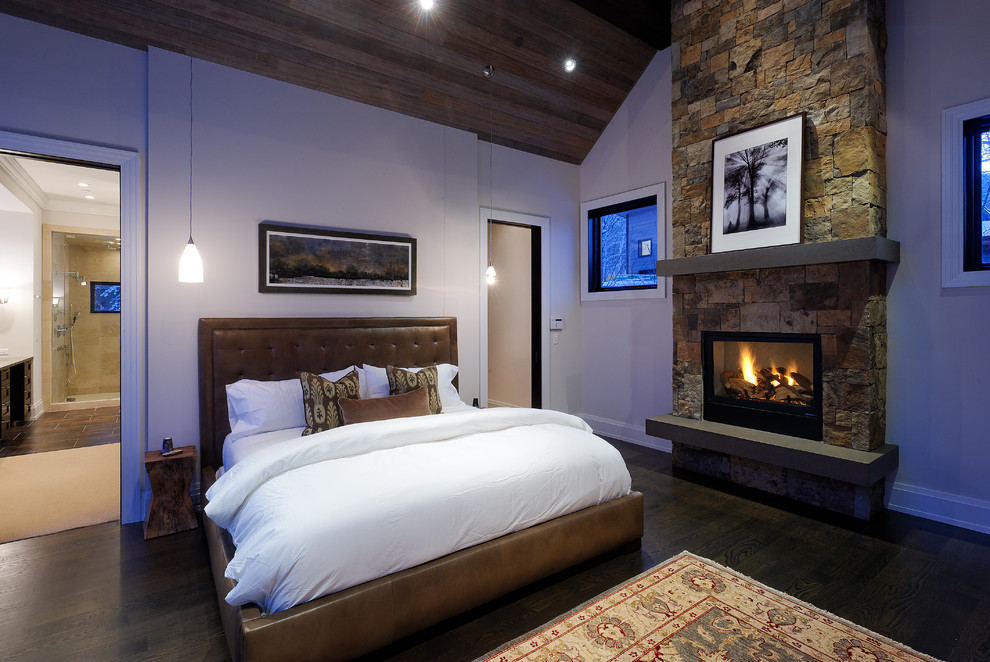 Bedroom - rustic bedroom idea in Denver with a stone fireplace and a standard fireplace