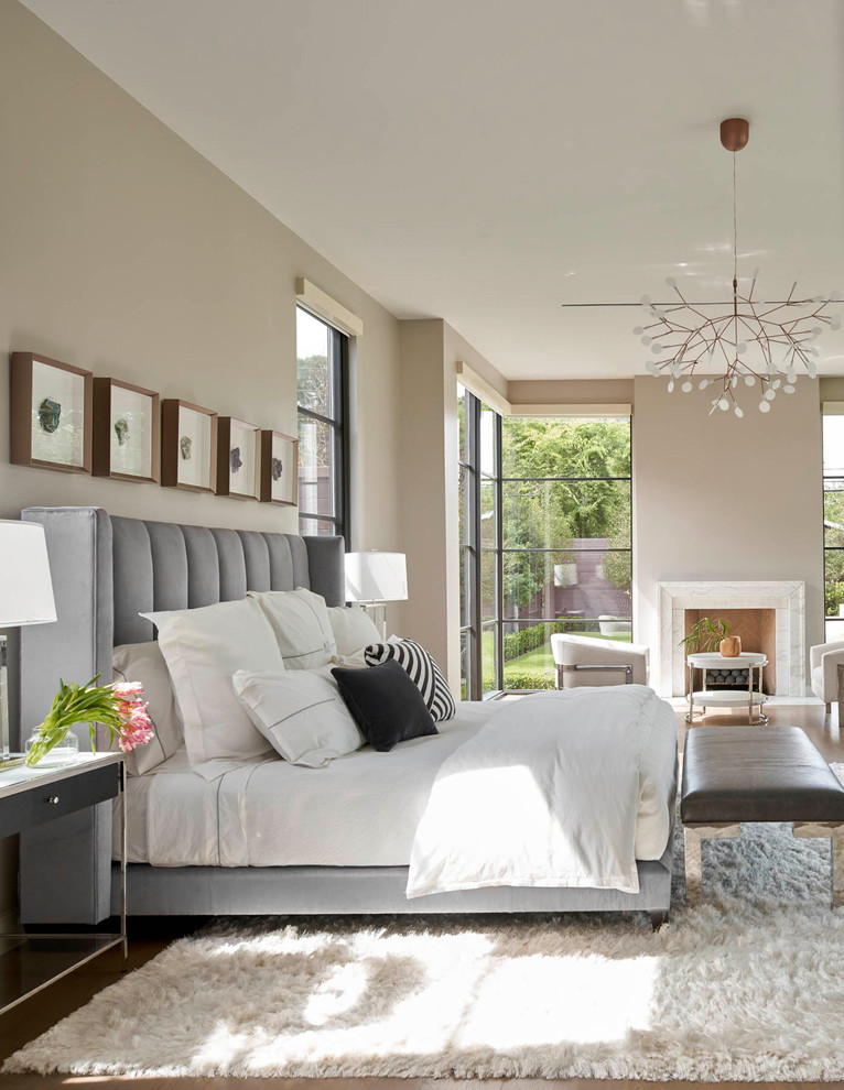 Trendy medium tone wood floor and brown floor bedroom photo in Dallas with beige walls and a standard fireplace