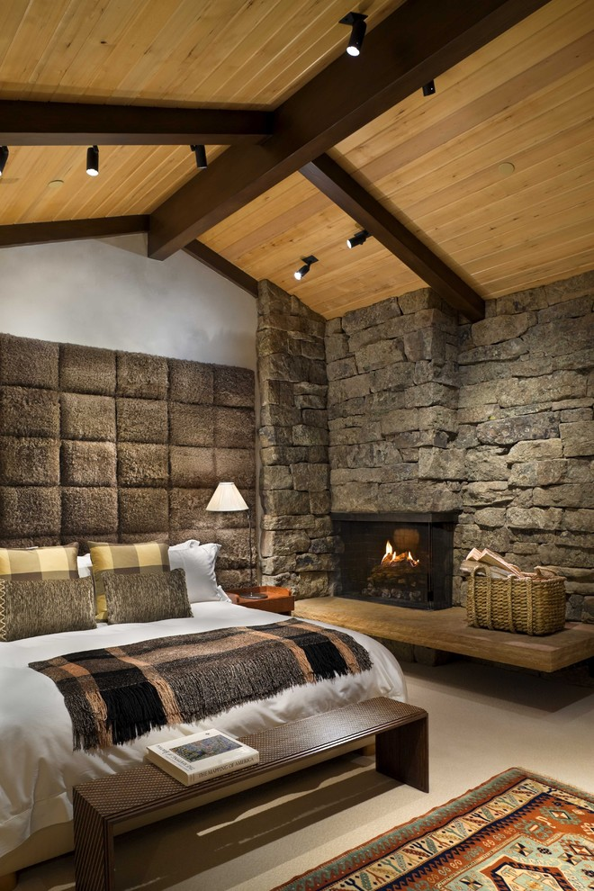 Bedroom - mid-sized rustic master concrete floor bedroom idea in New York with a stone fireplace, a corner fireplace and white walls