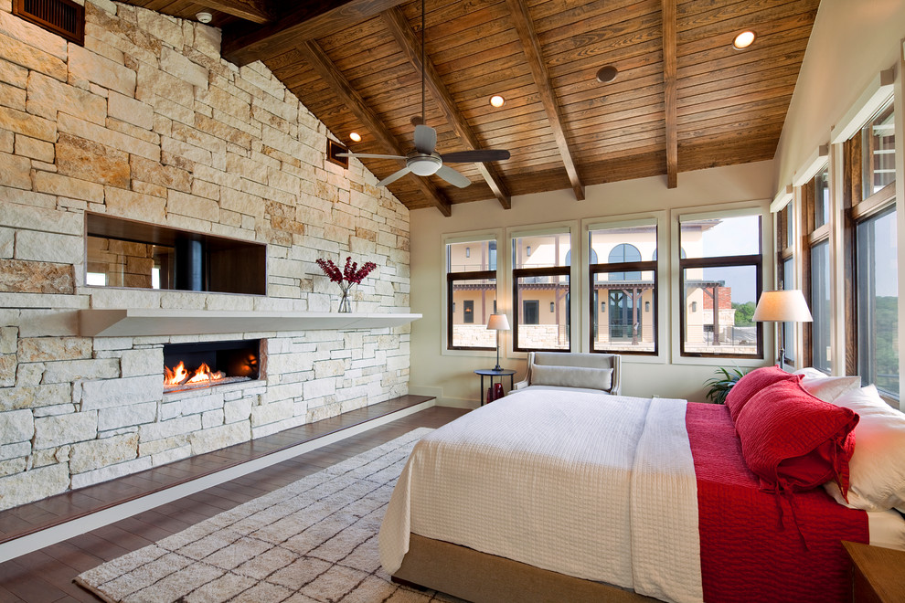 Tuscan dark wood floor bedroom photo in Austin with beige walls, a ribbon fireplace and a stone fireplace