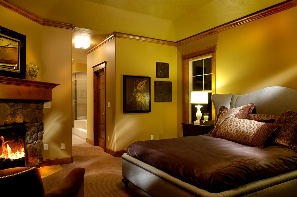 Mid-sized arts and crafts master carpeted bedroom photo in Seattle with yellow walls, a standard fireplace and a stone fireplace