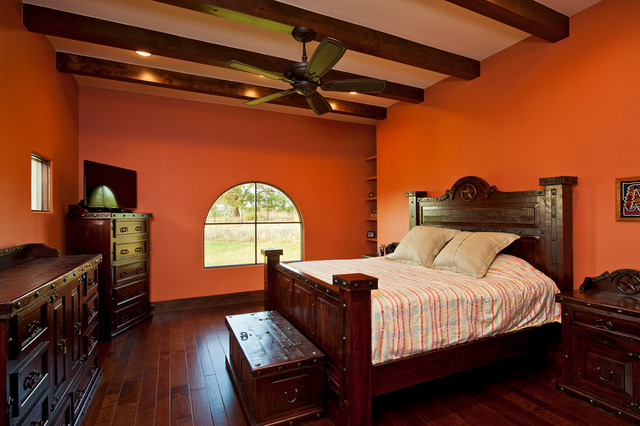 Master bedroom orange colored walls exposed beams hardwood for Mediterranean master bedroom
