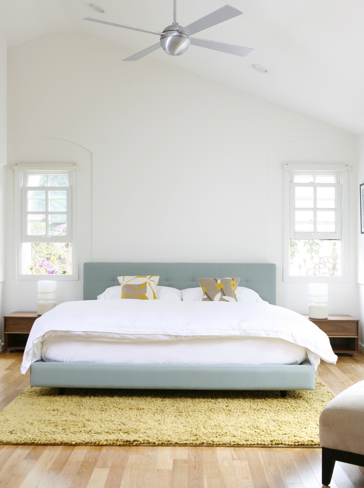 Example of a minimalist master light wood floor bedroom design in Los Angeles with white walls