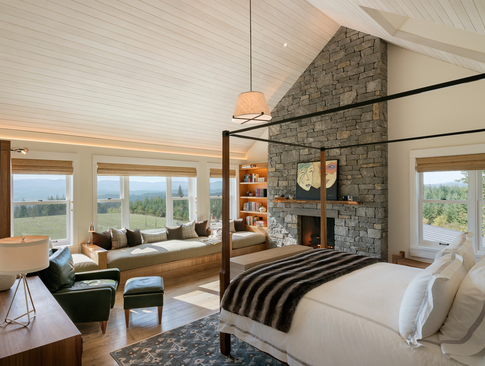 Example of a large cottage master medium tone wood floor and brown floor bedroom design in Other with beige walls, a standard fireplace and a stone fireplace