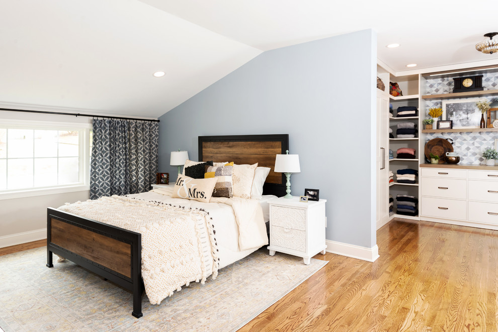 Inspiration for a large transitional master medium tone wood floor and brown floor bedroom remodel in Other with white walls and no fireplace