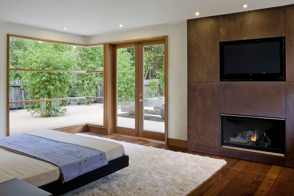 Bedroom - contemporary master dark wood floor bedroom idea in San Francisco with beige walls, a standard fireplace and a metal fireplace