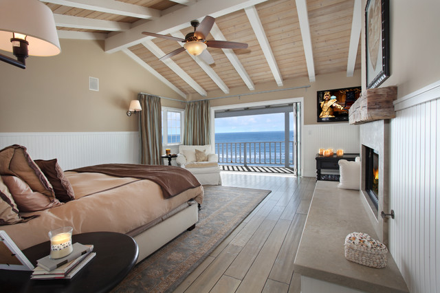 Coastal light wood floor bedroom photo in Orange County with beige walls and a standard fireplace