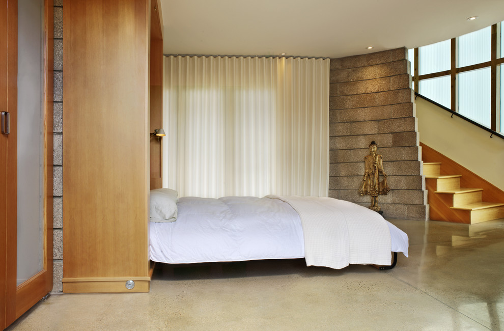 Inspiration for a contemporary concrete floor bedroom remodel in Denver with beige walls