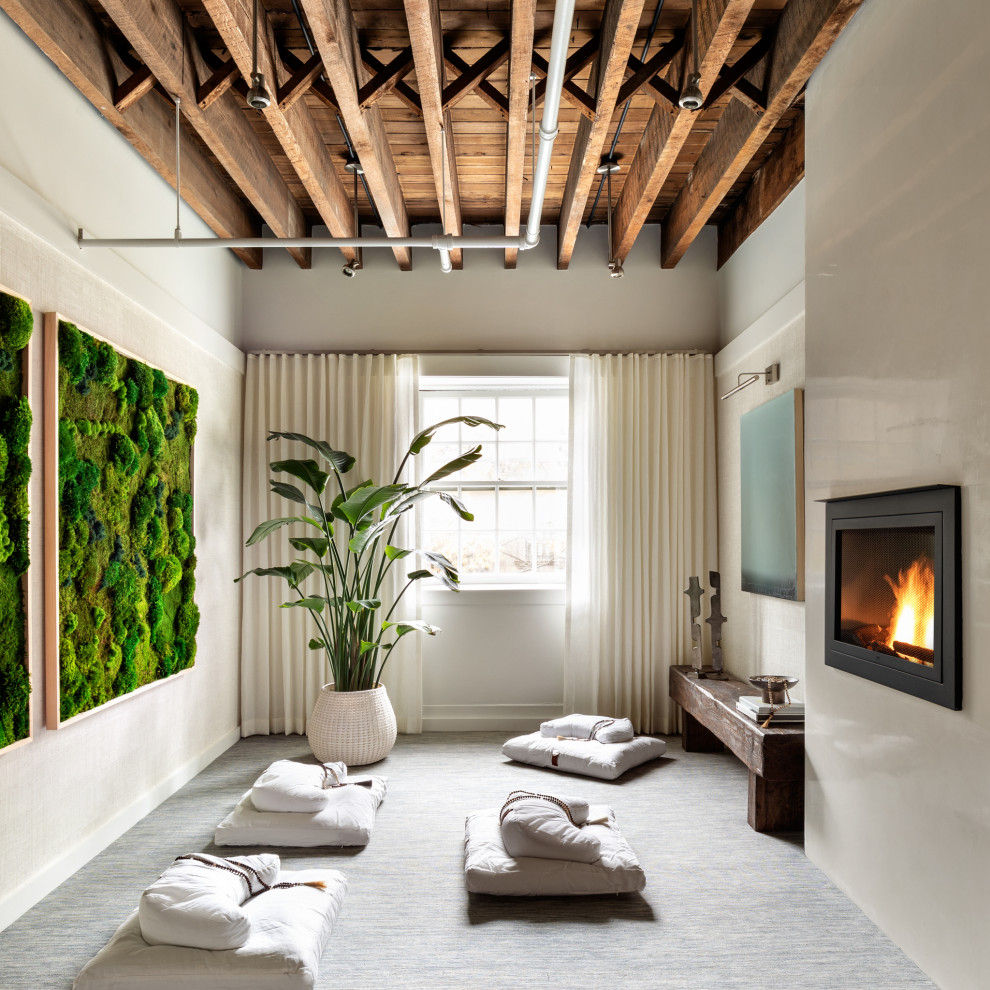 Example of a mid-sized trendy guest carpeted and blue floor bedroom design in New York with white walls, a hanging fireplace and a plaster fireplace