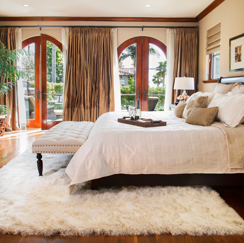 Bedroom - mediterranean master medium tone wood floor bedroom idea in Los Angeles with white walls