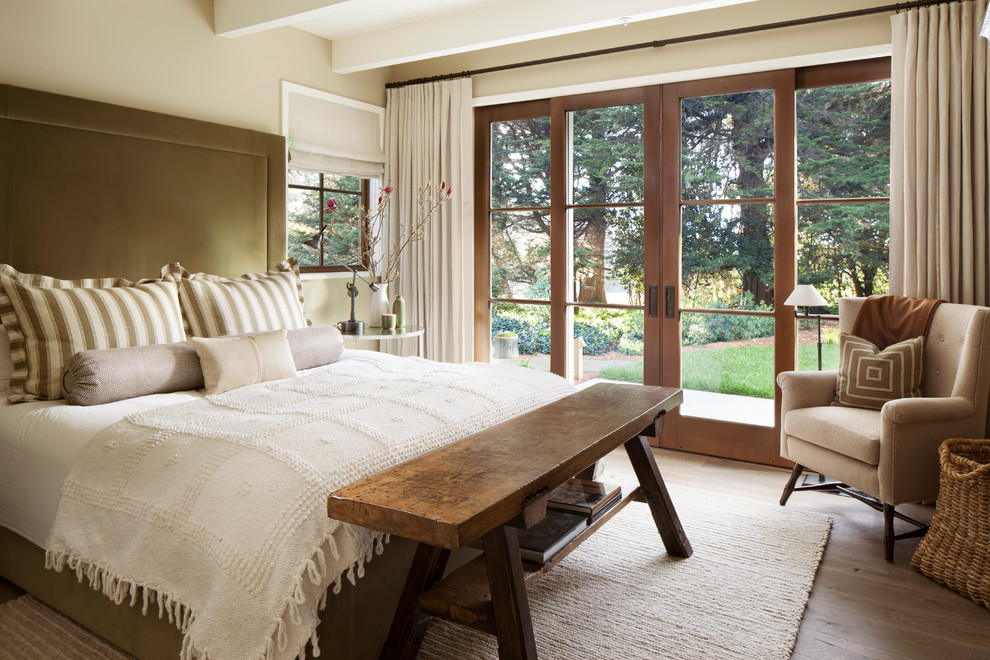 Example of a country master light wood floor bedroom design in San Francisco with beige walls