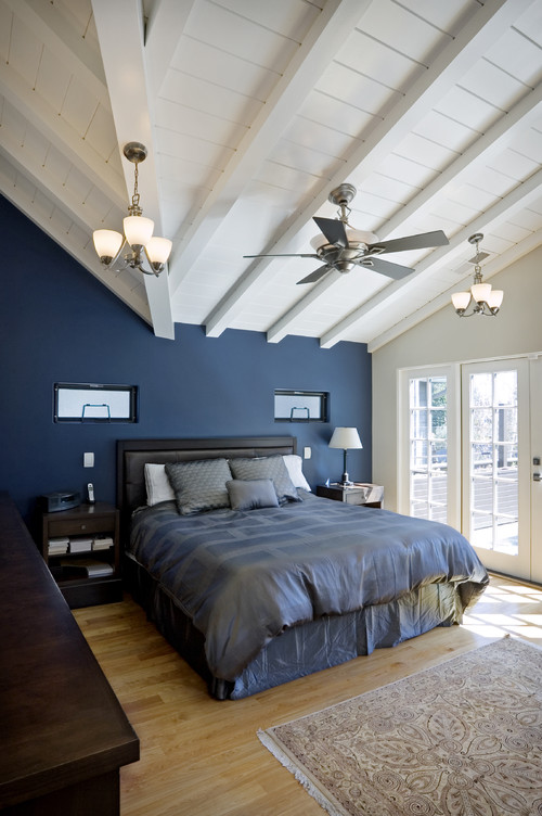 Dark Blue Bedroom Is Lightened With White Ceiling And Light Wood