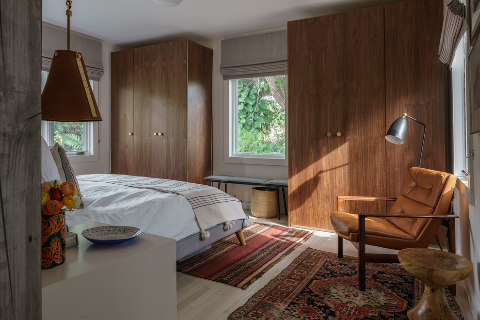 Example of a mid-century modern light wood floor and beige floor bedroom design in Miami with white walls