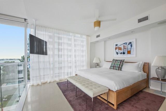 Bedroom - mid-sized contemporary master limestone floor bedroom idea in Miami with white walls
