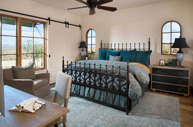 Example of a tuscan medium tone wood floor and brown floor bedroom design in Los Angeles with white walls