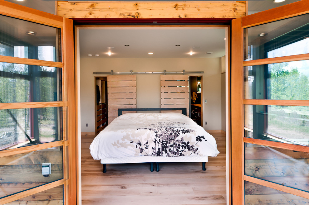 Inspiration for a contemporary light wood floor bedroom remodel in Denver with white walls