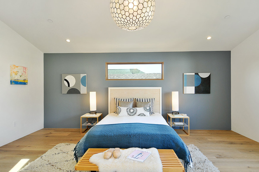 Example of a large trendy master light wood floor bedroom design in San Francisco with blue walls