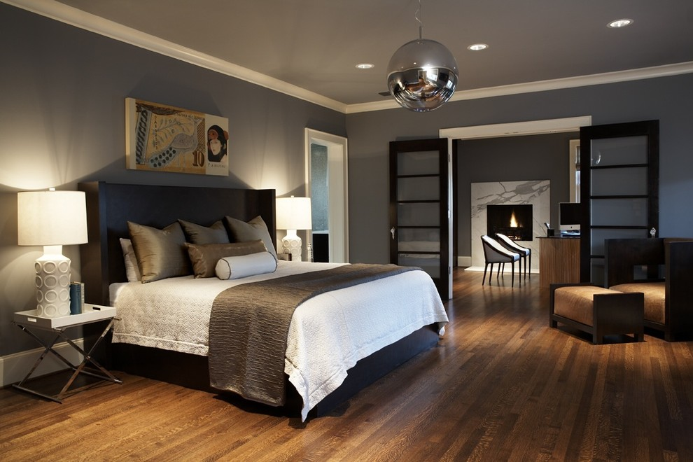 Example of a large trendy master dark wood floor and brown floor bedroom design in Seattle with gray walls and no fireplace