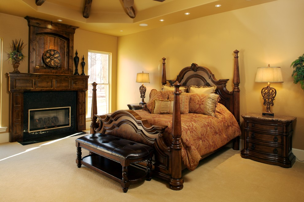 Example of a mid-sized tuscan master carpeted bedroom design in Dallas with beige walls, a standard fireplace and a wood fireplace surround