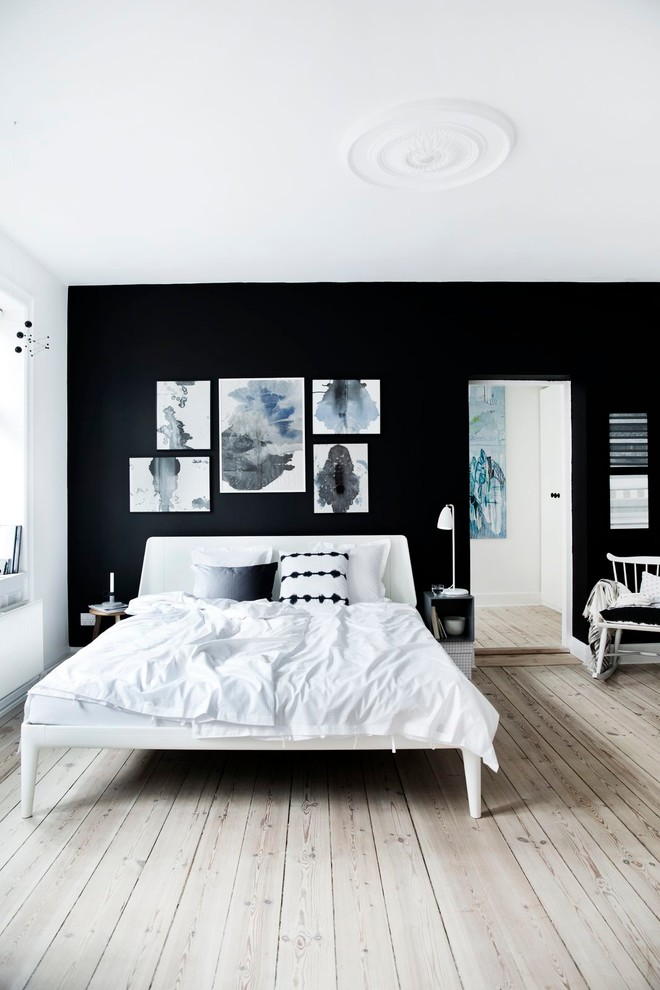 Mid-sized danish master light wood floor bedroom photo in Other with black walls