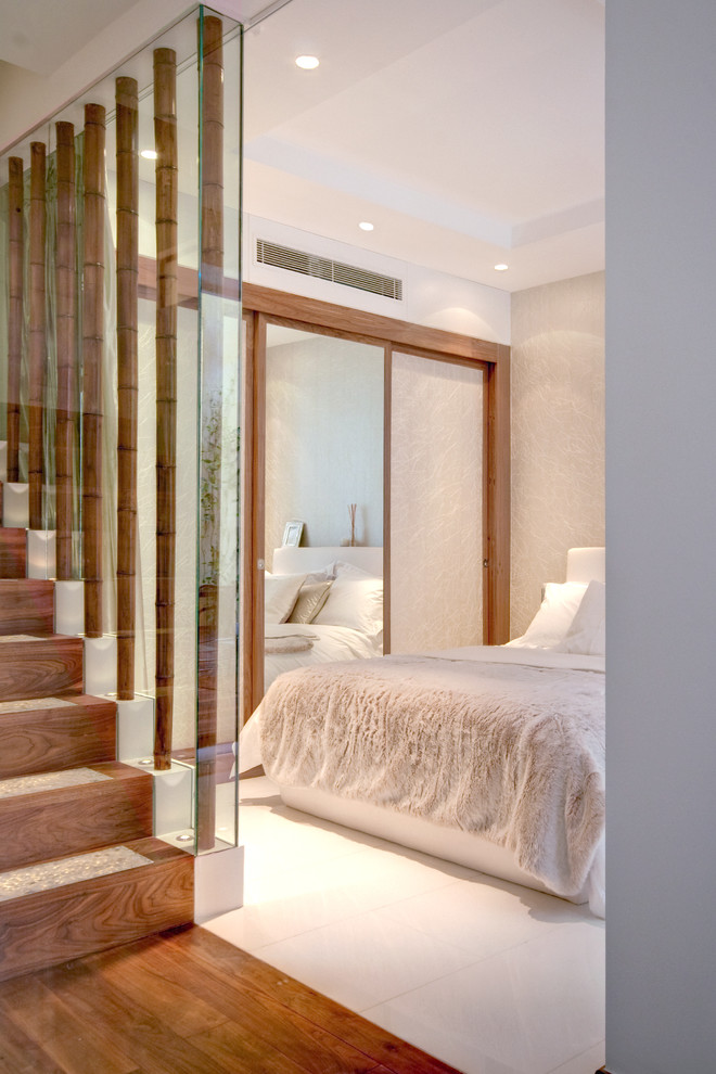 Example of a large trendy master bedroom design in London with beige walls and no fireplace