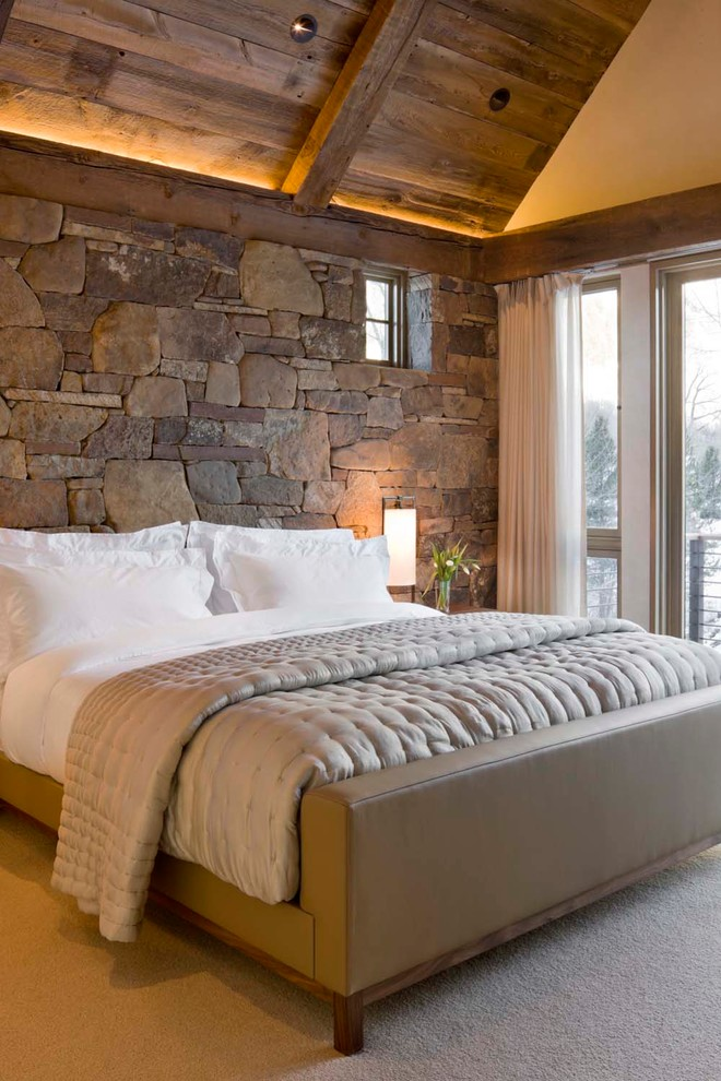Example of a mountain style carpeted bedroom design in Denver with no fireplace