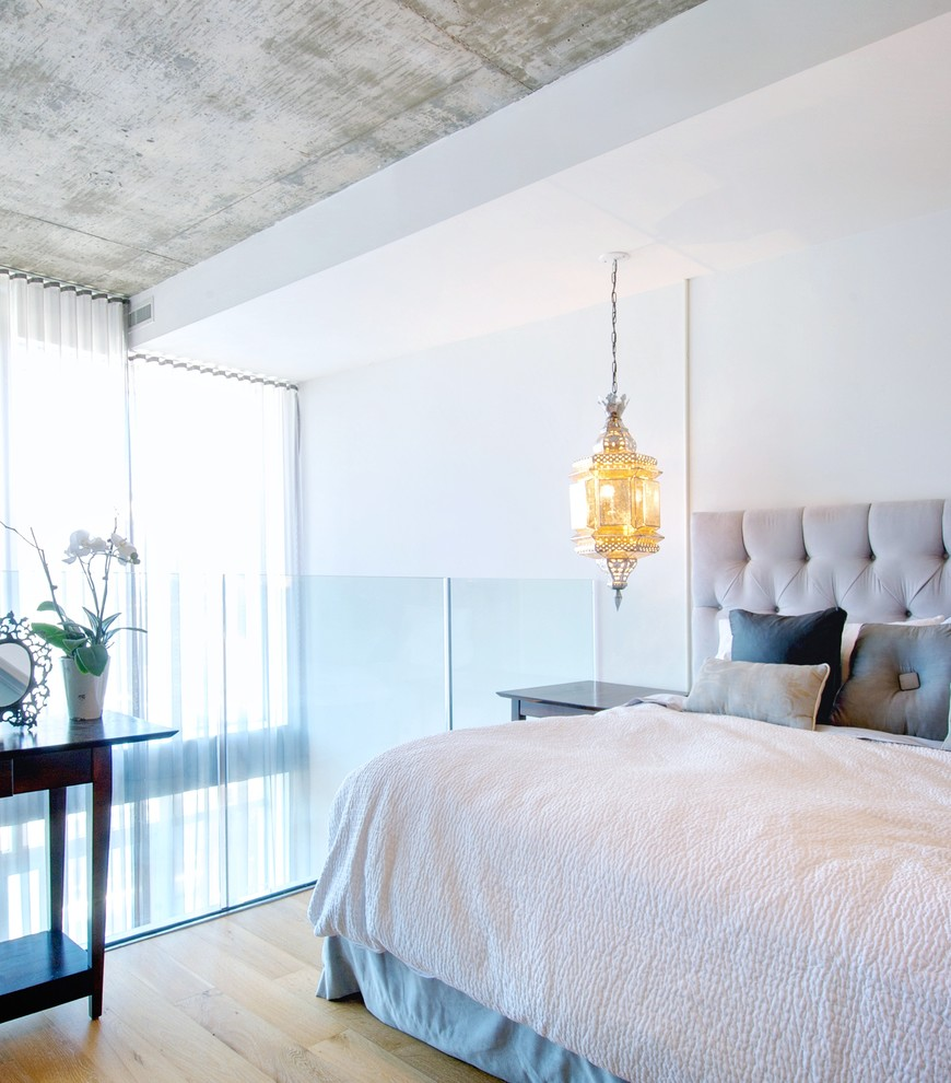 Bedroom - contemporary loft-style light wood floor bedroom idea in Toronto with white walls