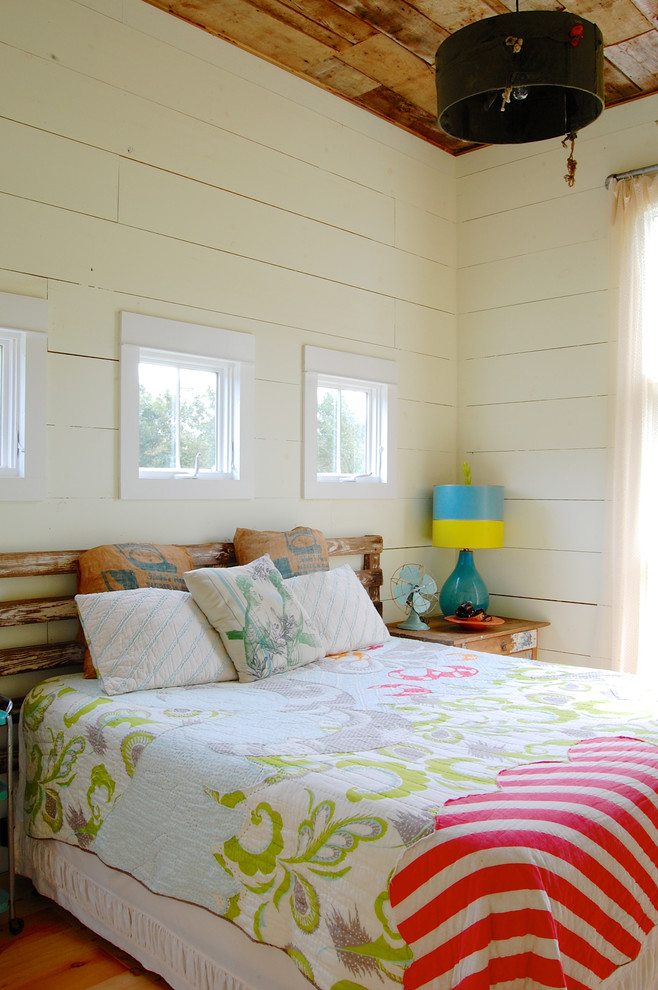 Example of a cottage medium tone wood floor bedroom design in New York with white walls and no fireplace