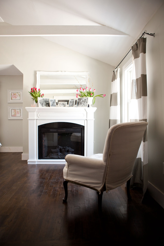 Example of a classic dark wood floor bedroom design in Boston with beige walls and a standard fireplace