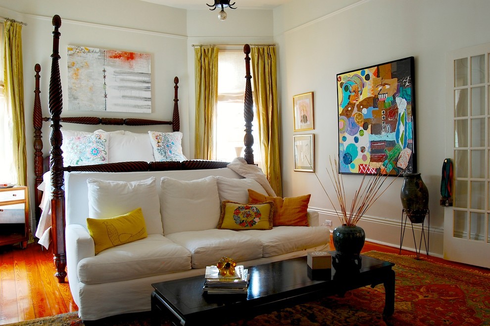 Example of an eclectic master medium tone wood floor bedroom design in New York with white walls and no fireplace