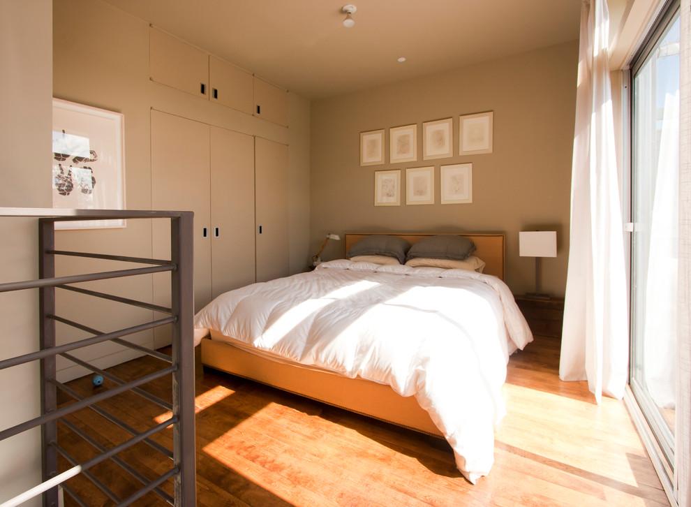 Bedroom - industrial medium tone wood floor bedroom idea in New York with beige walls