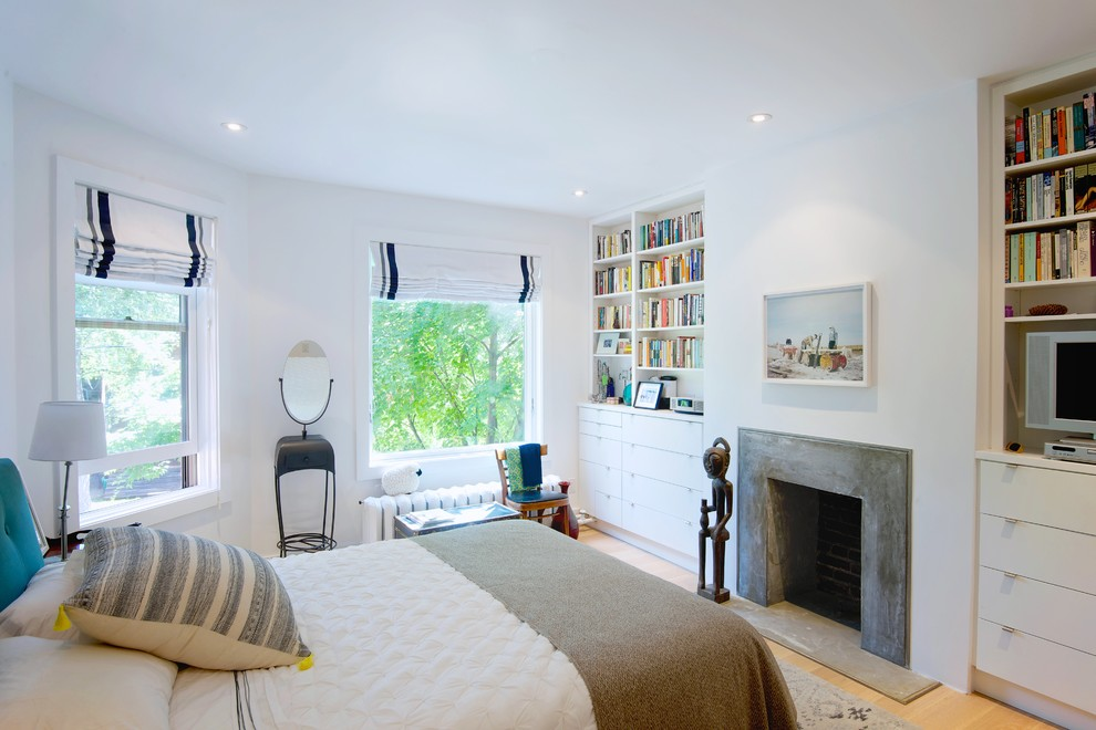 Example of a mid-sized danish master light wood floor bedroom design in Toronto with white walls, a standard fireplace and a concrete fireplace