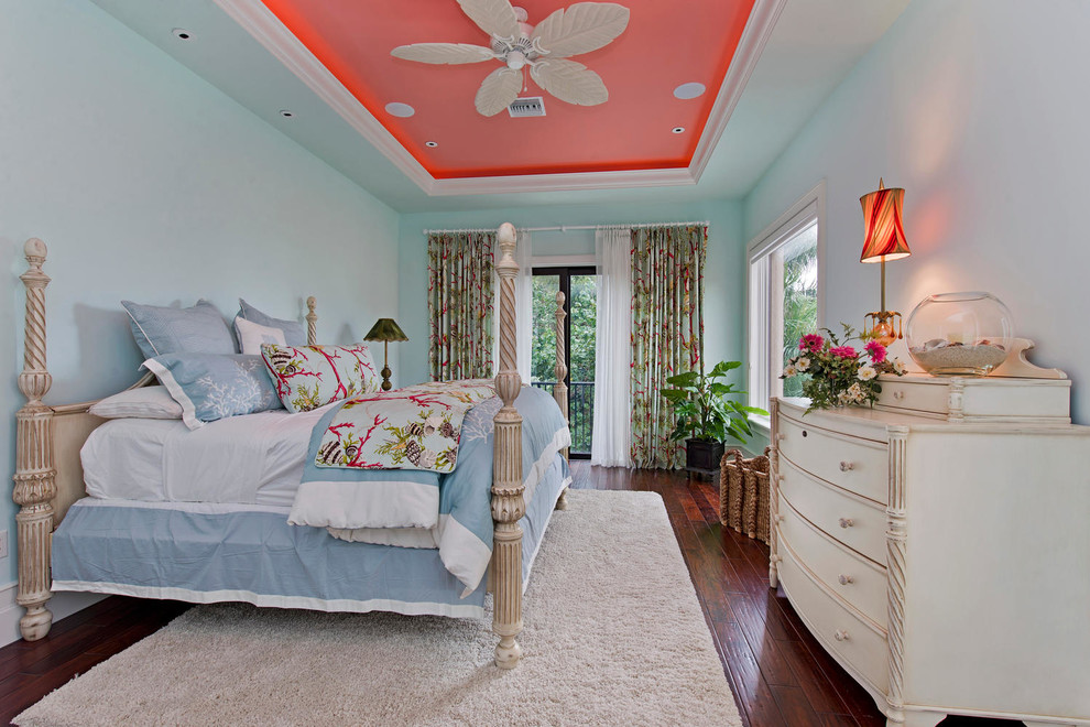 Example of an island style dark wood floor bedroom design in Miami with blue walls