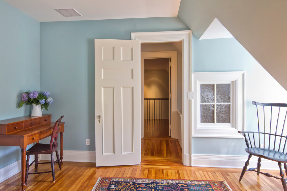 Inspiration for a timeless guest medium tone wood floor bedroom remodel in New York with blue walls